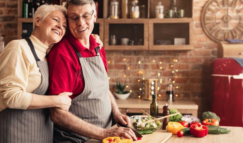Grateful senior woman hugging her husband at kitchen royalty free stock photos
