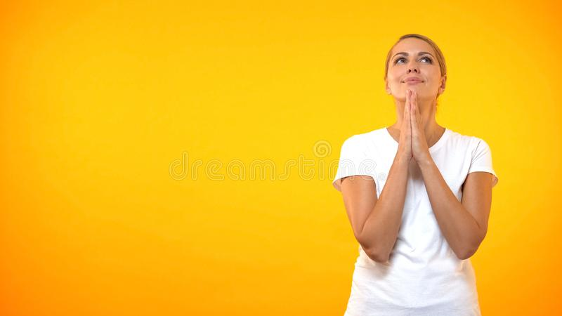 Grateful young lady joining hands looking up, dreaming female, waiting miracle stock images
