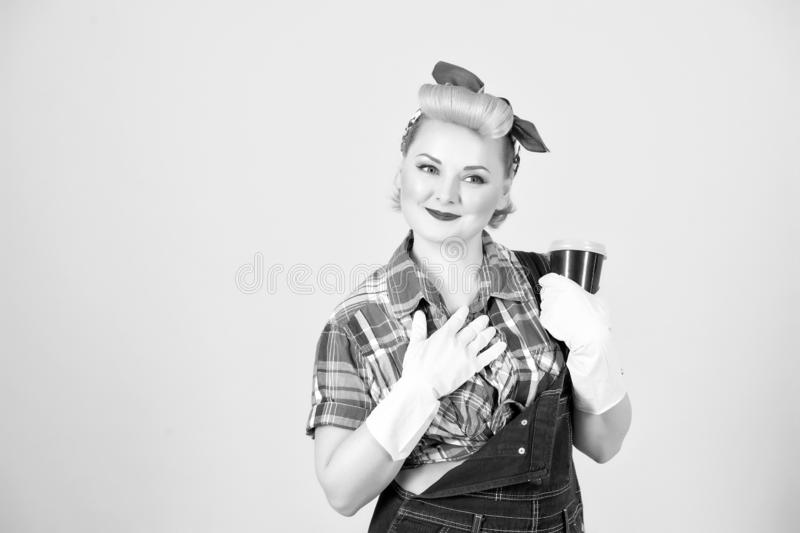 Housewife holding craft cup. thankful woman in rubber gloves with coffee cup in hand in retro pin-up style. Blonde girl thanks for royalty free stock photo