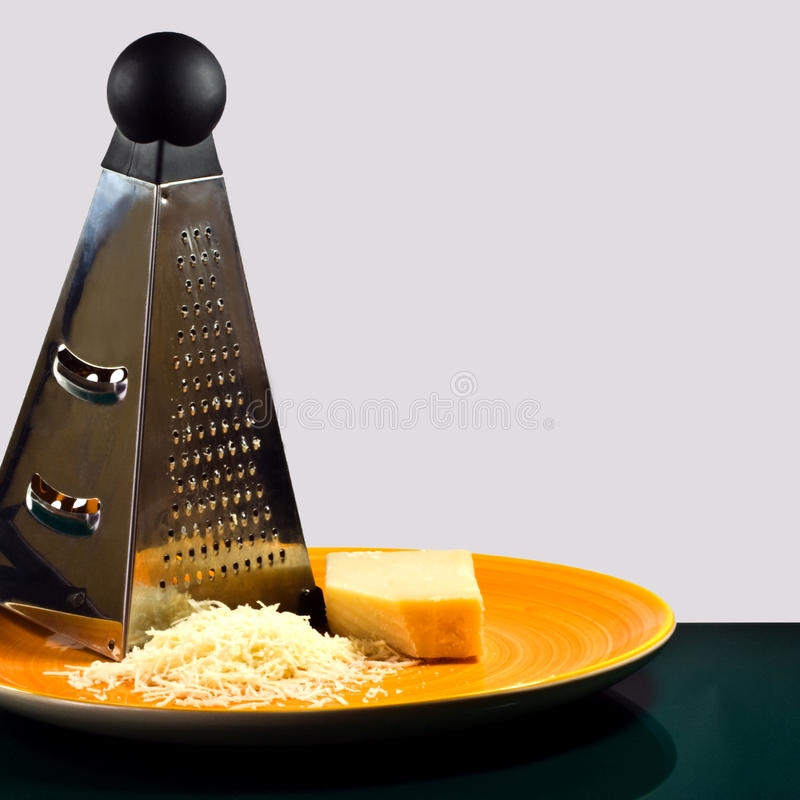 Grater and parmesan. A grater with parmesan cheese on an orange plate stock photo