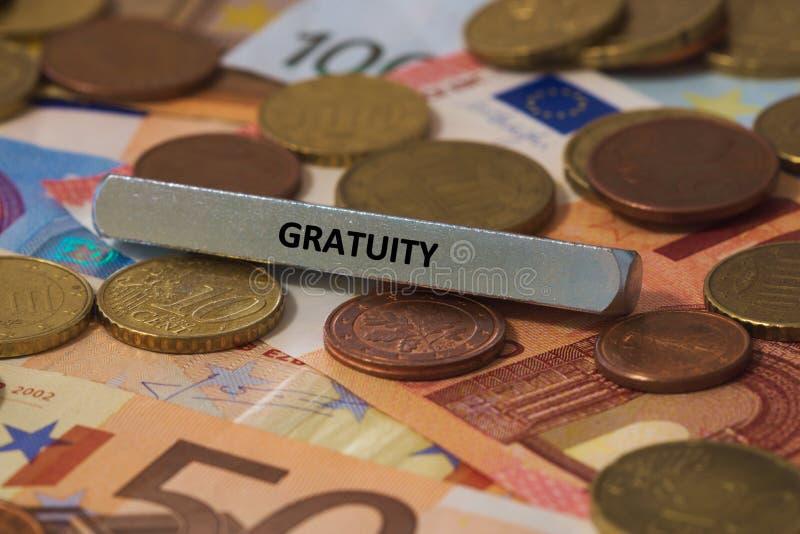 Gratifikation - das Wort wurde auf einer Metallstange gedruckt die Metallstange wurde auf einige Banknoten gesetzt lizenzfreies stockbild