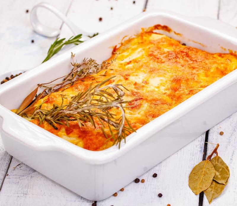 Gratin картошки в белом блюде сотейника на деревянной деревенской таблице стоковые фотографии rf