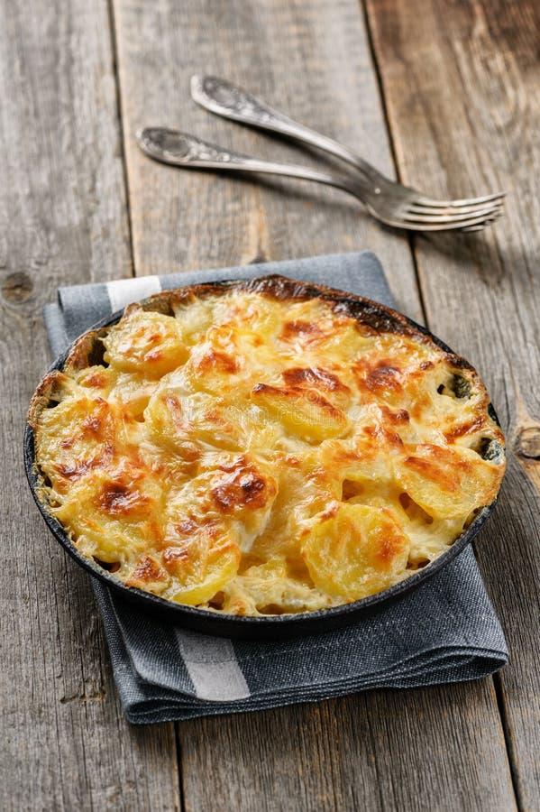 Gratin картошки в сотейнике с сливк и сыром стоковые изображения