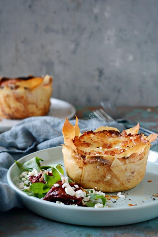 Gratin da batata cozido na massa do filo, com a crosta friável do queijo e com uma salada da rúcula, de tomates sol-secados e d fotografia de stock