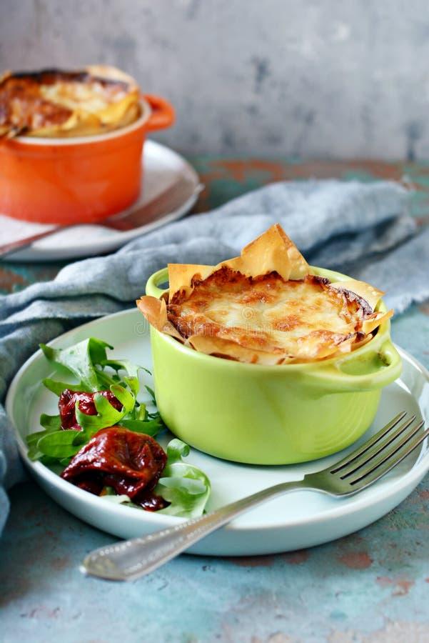 Gratin da batata cozido na massa do filo, com a crosta friável do queijo e com uma salada da rúcula, de tomates sol-secados e d foto de stock