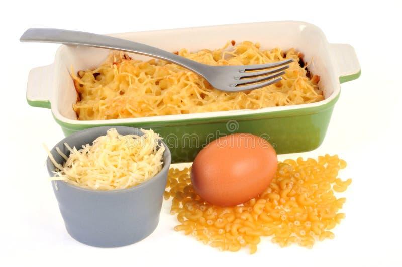 Gratin della pasta con i suoi ingredienti su un fondo bianco fotografia stock