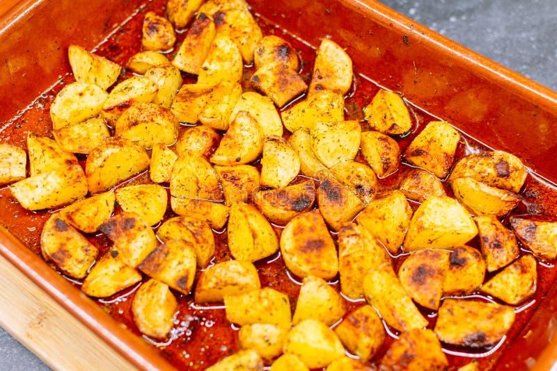 Gratin potatoes in red bowl preparing. Close up royalty free stock photo