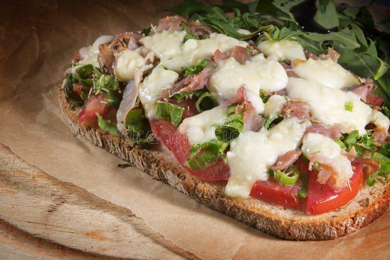 Gratinatedbrood met tomaat, de lenteuien, bacon en mozzarell stock foto