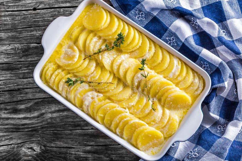 Gratinerade Dauphinois, potatisar bakade i en pannanärbild arkivfoto