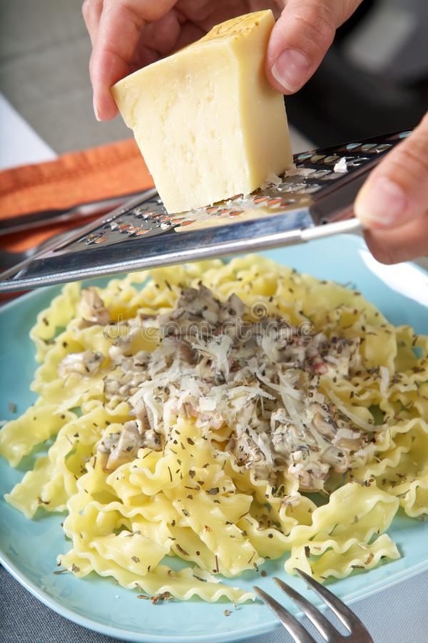 Download Grating Cheese On Pasta Royalty Free Stock Photography - Image: 26594087