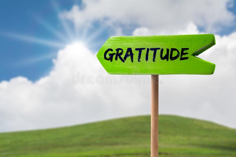Gratitude arrow sign. Gratitude green wooden arrow sign on green land with clouds and sunshine stock photo