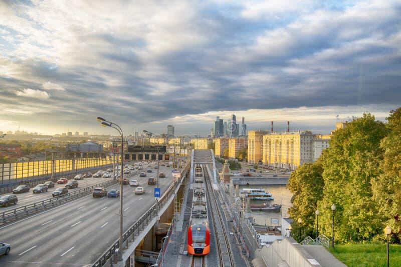 Grattacieli, terzo Ring Road e ES2G Lastochka & x28; Swallow& x29; i treni sul cerchio centrale di Mosca allineano al tramonto fotografia stock
