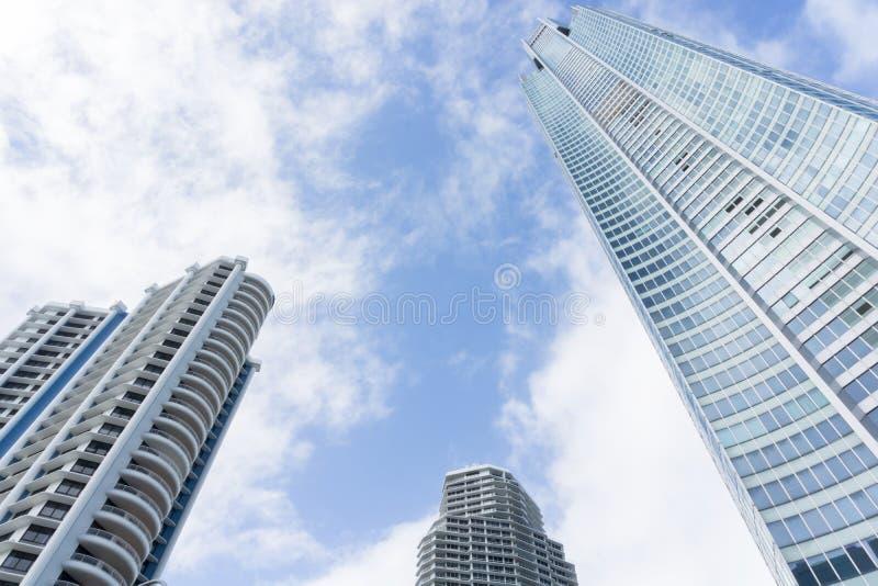 Grattacieli torreggianti con le nuvole che vanno alla deriva vicino immagini stock