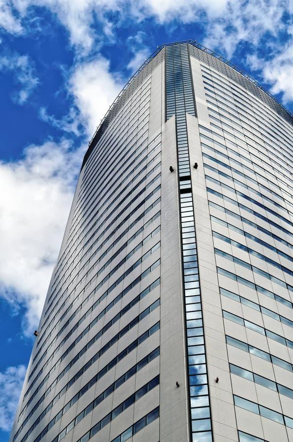 Grattacielo moderno sul fondo nuvoloso del cielo blu fotografia stock