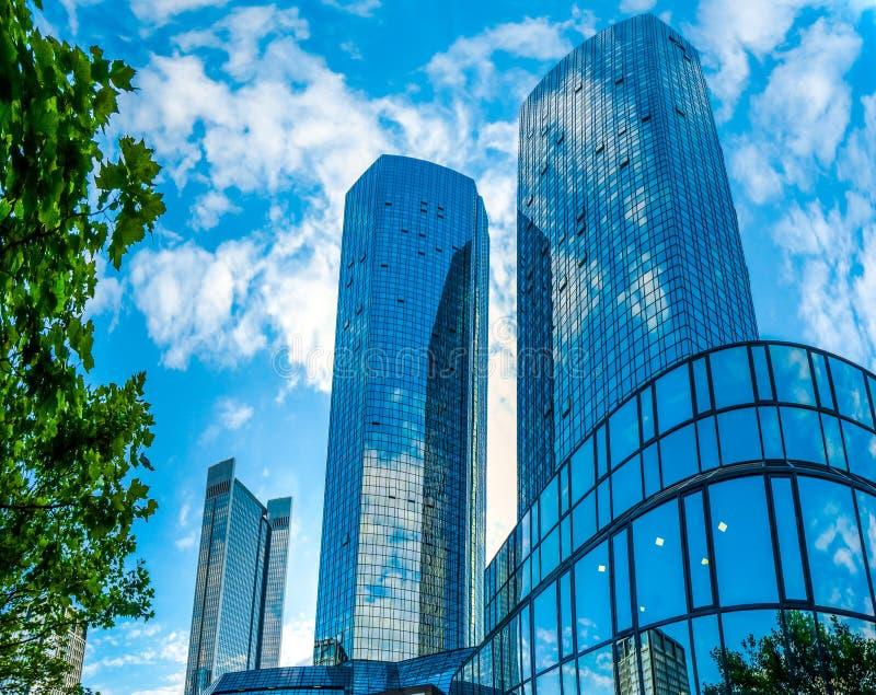 Gratte-ciel modernes au district des affaires contre le ciel bleu photos stock