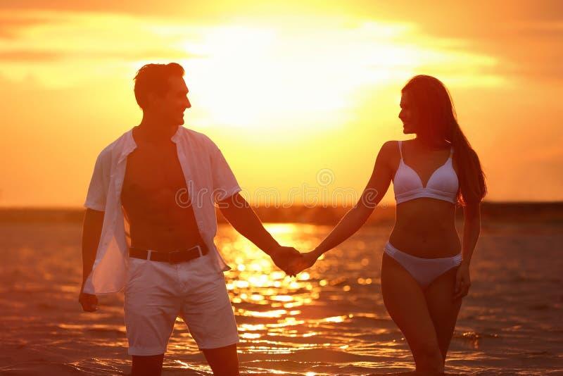 Grattis på det unga par som spenderar tid på havsstranden vid solnedgången royaltyfri bild