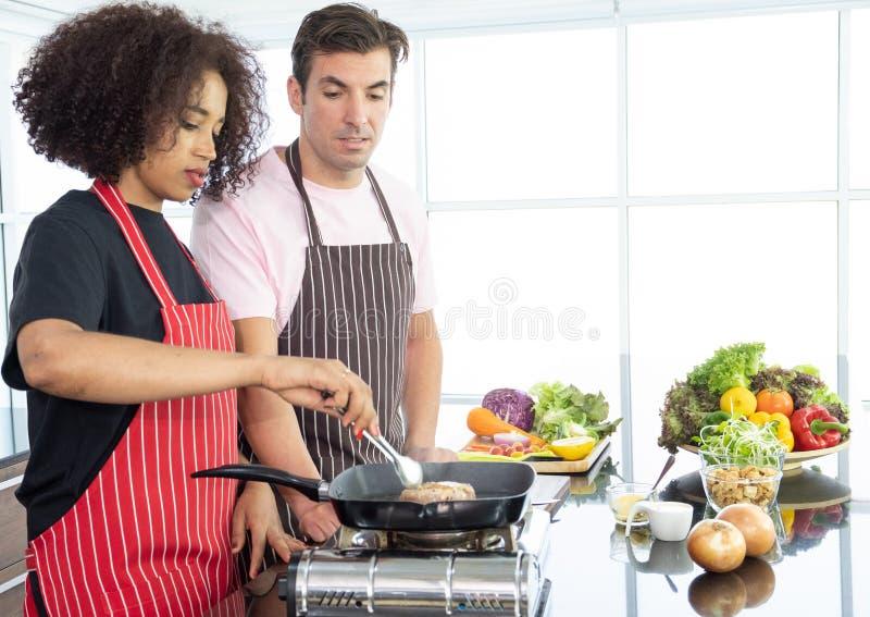 Grattis på ditt unga par när du lagar mat tillsammans arkivbild