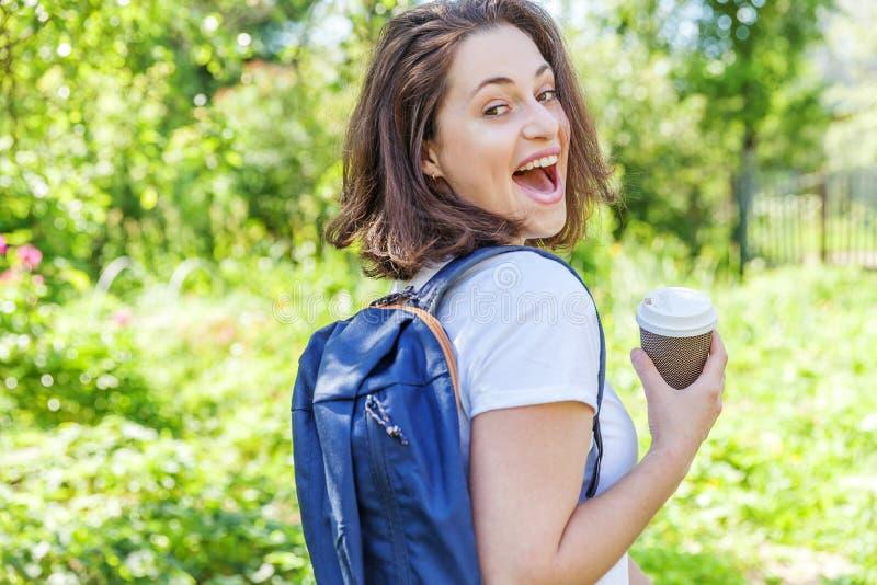 Grattis på en positiv studenttjej med ryggsäck och ta bort kaffekopp som leker på grönparkens bakgrund royaltyfria foton