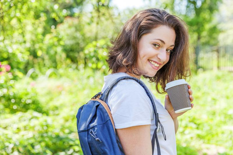 Grattis på en positiv studenttjej med ryggsäck och ta bort kaffekopp som leker på grönparkens bakgrund arkivfoto