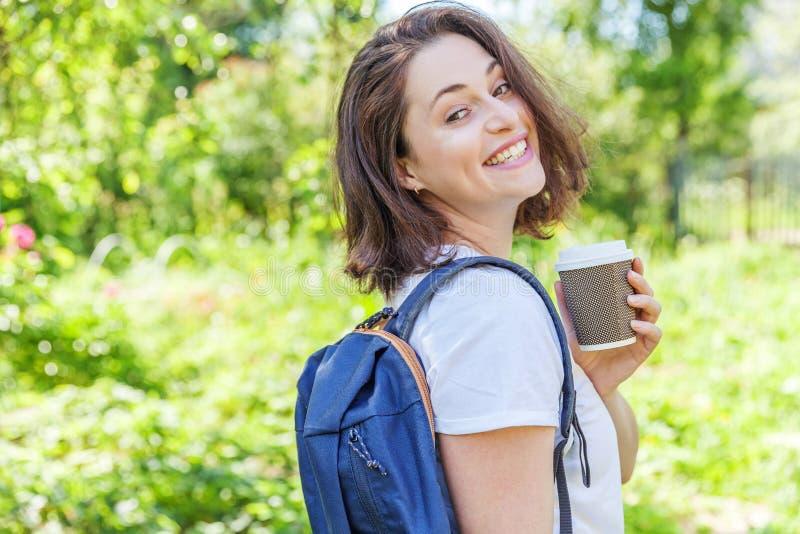 Grattis på en positiv studenttjej med ryggsäck och ta bort kaffekopp som leker på grönparkens bakgrund fotografering för bildbyråer