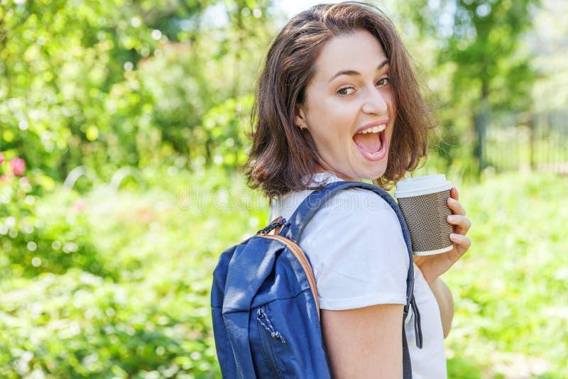 Grattis på en positiv studenttjej med ryggsäck och ta bort kaffekopp som leker på grönparkens bakgrund royaltyfri bild