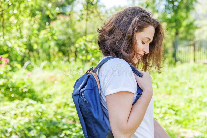 Grattis på en positiv studenttjej med ryggsäck som leker på grön parks bakgrund royaltyfria bilder