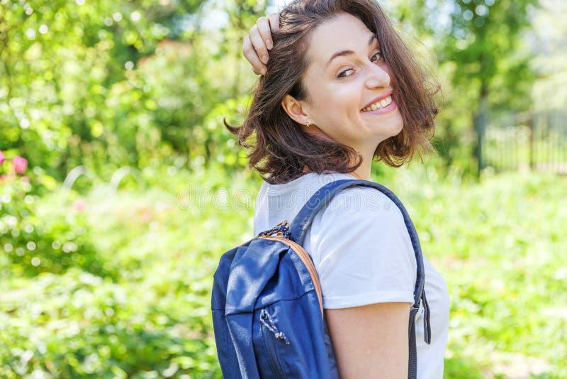 Grattis på en positiv studenttjej med ryggsäck som leker på grön parks bakgrund royaltyfri foto