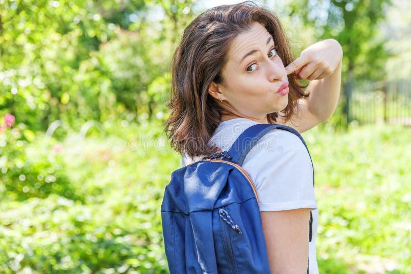 Grattis på en positiv studenttjej med ryggsäck som leker på grön parks bakgrund arkivfoto