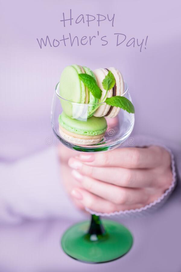 Grattis på moderns hälsningskort Honhand som håller glas med makaroner på ljusviolett bakgrund arkivbild
