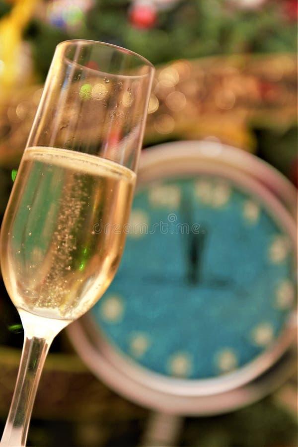 Grattis på nytt år med champagneglas som väntar midnatt och tittar royaltyfri fotografi