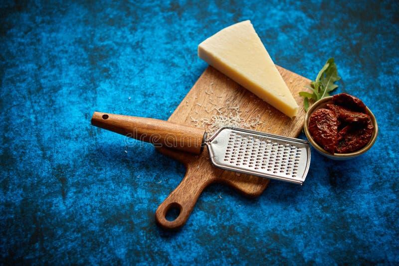 Grattugia classica grattata del metallo e del parmigiano disposta sul tagliere di legno immagine stock libera da diritti