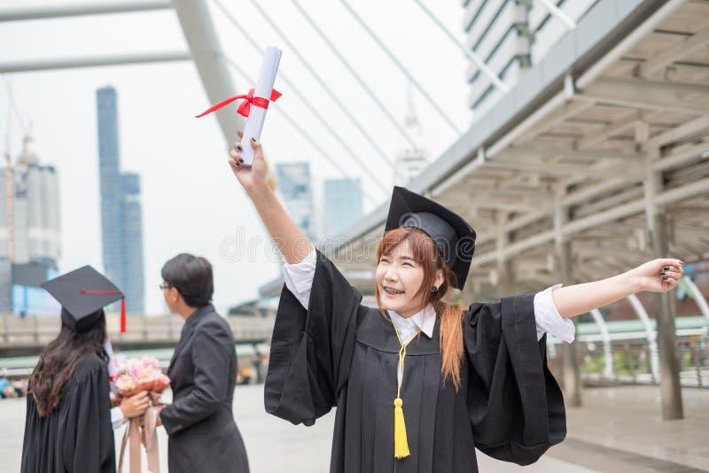 Grau graduado do ` s do licenciado da mulher que guarda o diploma com engodo dos pares fotos de stock