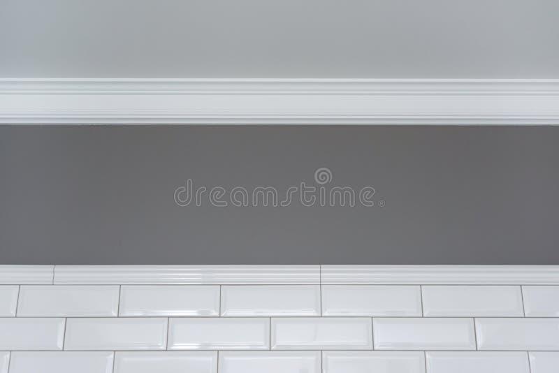 Grau malte Wand, weißes Deckenformteil und kleinen weißen glatten Ziegelstein der keramischen dekorativen Fliesen Fragment der Wä lizenzfreie stockbilder