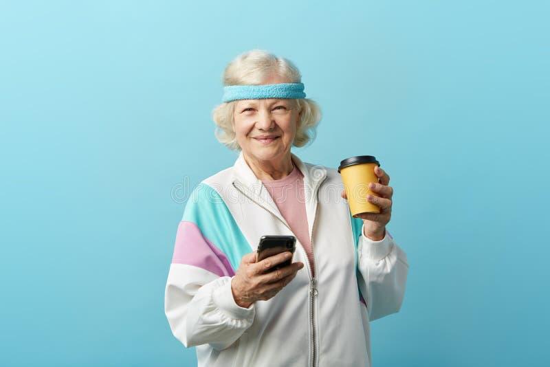 Graue behaarte reife Frau im Stirnband und in der wei?en Sportjacke, hat Kaffeepause lizenzfreies stockfoto