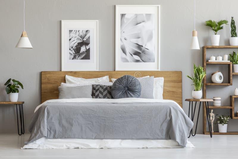 Graue Blätter und Kissen auf hölzernem Bett im Schlafzimmerinnenraum mit lizenzfreie stockfotos