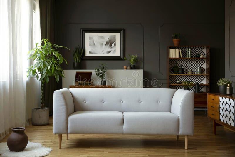 Graue Couch im Weinlesewohnzimmerinnenraum mit hölzernem Schrank, Plakat und Anlage Reales Foto stockfoto