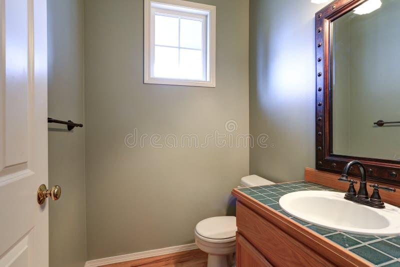 Graue Damentoilette bietet Eitelkeitskabinett mit grüner mit Ziegeln gedeckter Gegenspitze an lizenzfreie stockfotografie