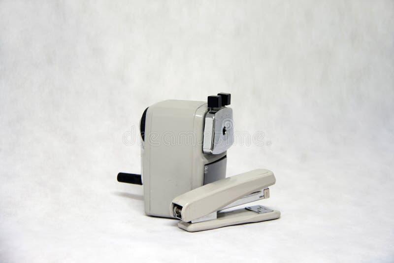 Graue Farbe des Bleistiftspitzers und des Hefters lokalisiert auf weißem Gewebehintergrund stockfoto