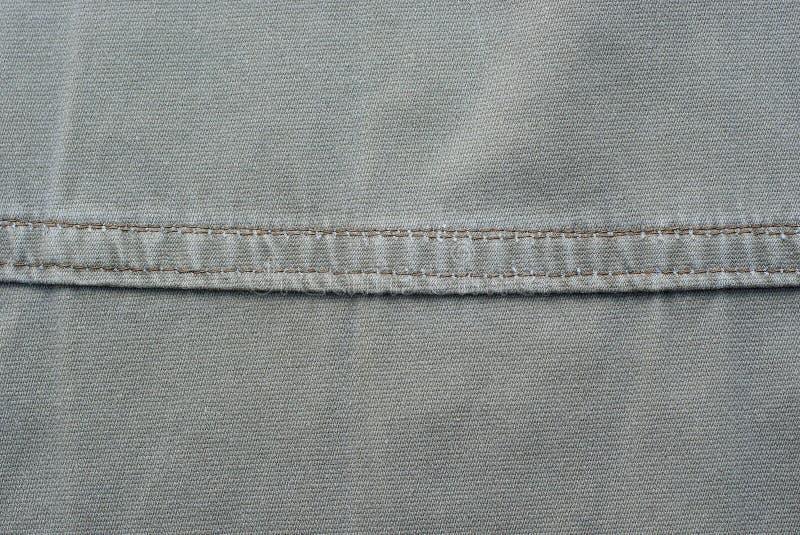 Graue Gewebebeschaffenheit eines Stückes Baumwoll-Kleidungs stockbild