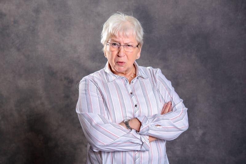 Graue haarige ältere Frau mit den gekreuzten Armen, die verärgert schauen lizenzfreies stockfoto