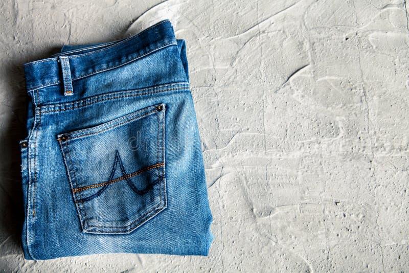 Graue Jeans auf einer Draufsicht des konkreten Hintergrundes lizenzfreie stockfotografie