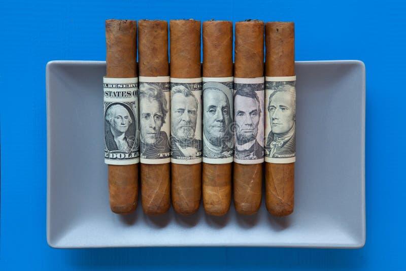 Graue keramischen kubanische Zigarren des Tellers und des Luxus mit US-Dollar banknot lizenzfreie stockfotografie