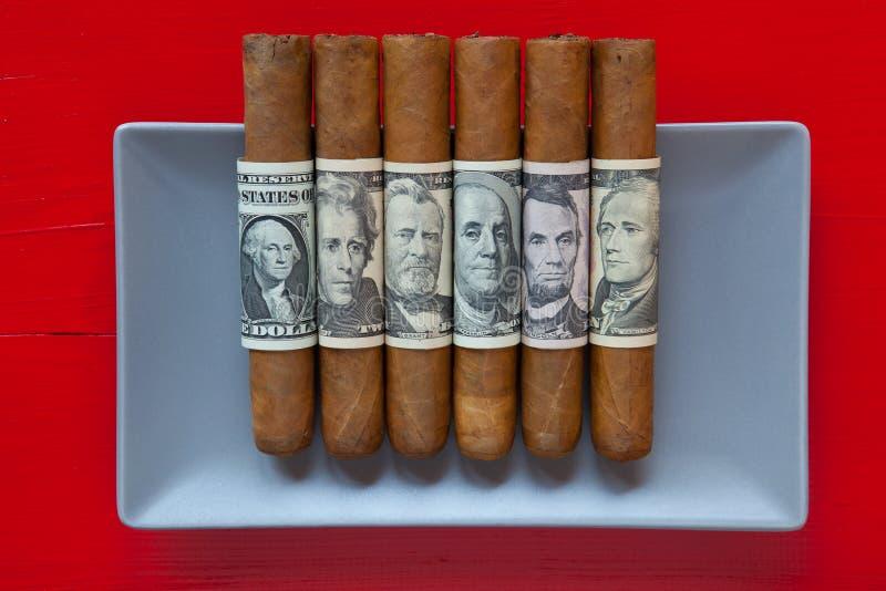 Graue keramischen kubanische Zigarren des Tellers und des Luxus mit US-Dollar banknot stockfotos