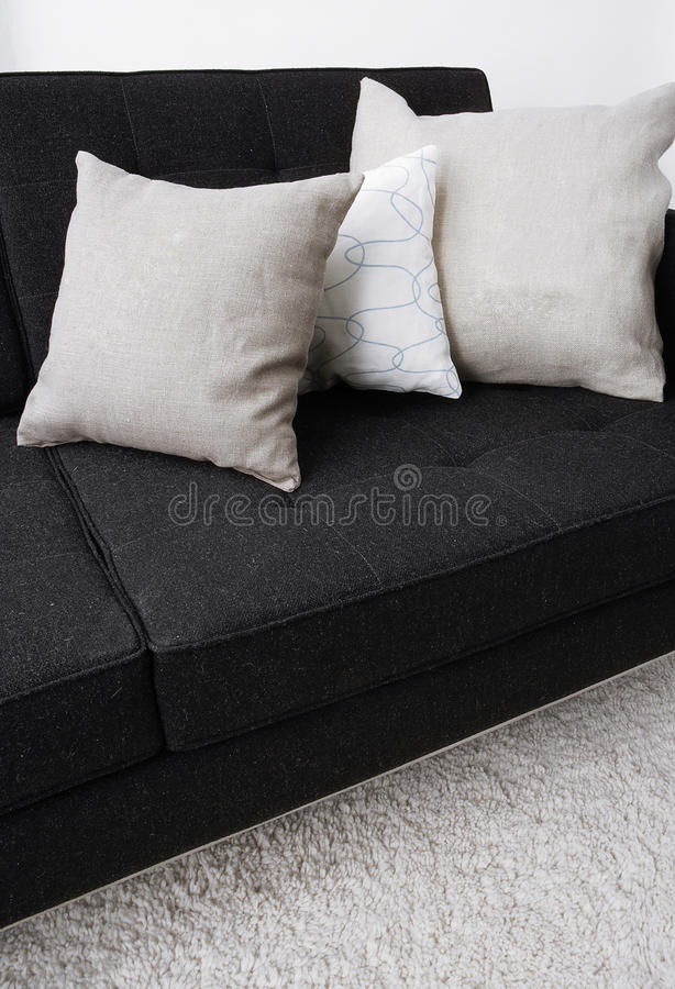 graue kissen die auf ein schwarzes sofa legen stockfoto. Black Bedroom Furniture Sets. Home Design Ideas