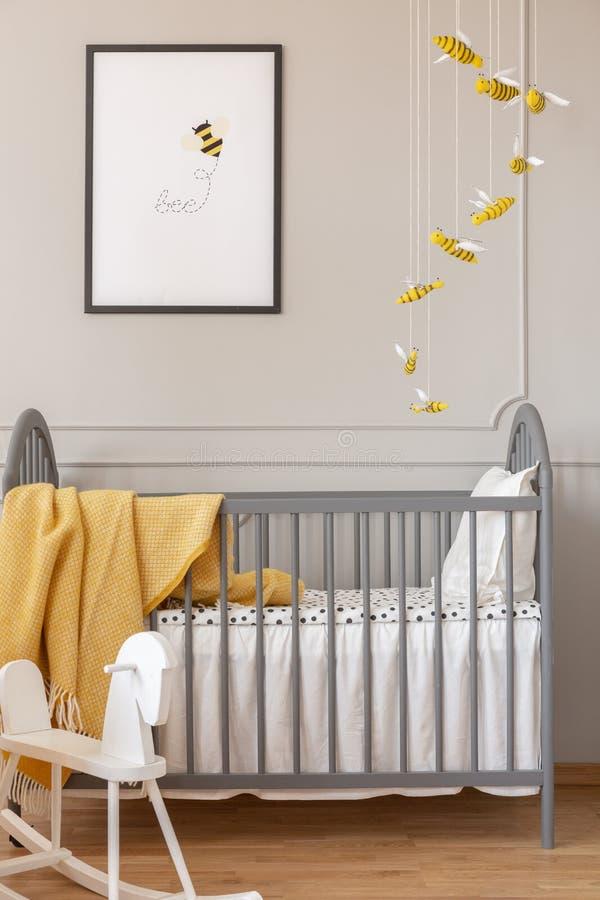 Graue Krippe, Bienendekoration und -graphik und Schaukelpferd in einem Kinderraum stockfoto