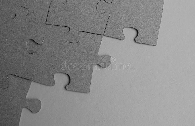 Graue Puzzlespiele breiteten auf dem Tisch auf einem grauen Hintergrund aus stockbilder
