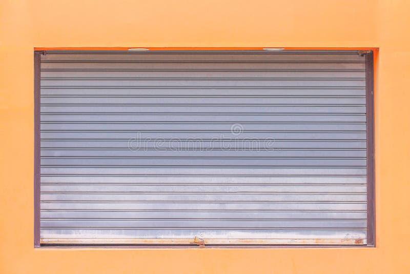 Graue rollende Stahltür oder Rollenfensterladentür mit Vorhängeschloß auf orange Wandhintergrund, Metallmuster stockbild