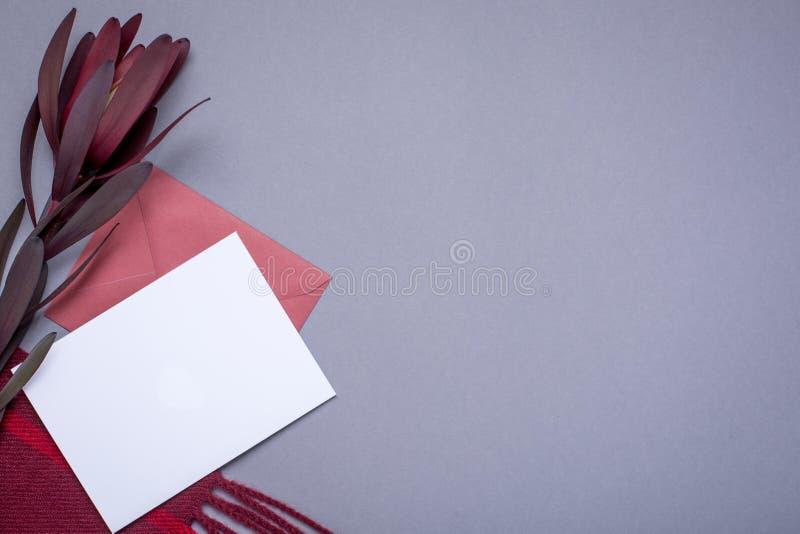 Graue Tapete mit Geschenkkarte und Burgunder-Verpackung lizenzfreie stockfotografie