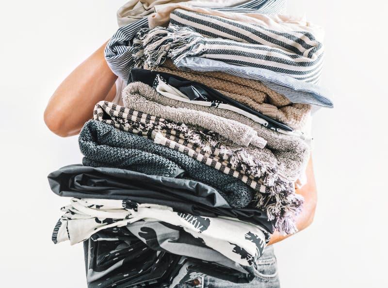 Graue und beige Wäscherei des großen Stapels in den Frauenhänden nah herauf Bild auf weißem Hintergrund lizenzfreie stockfotos
