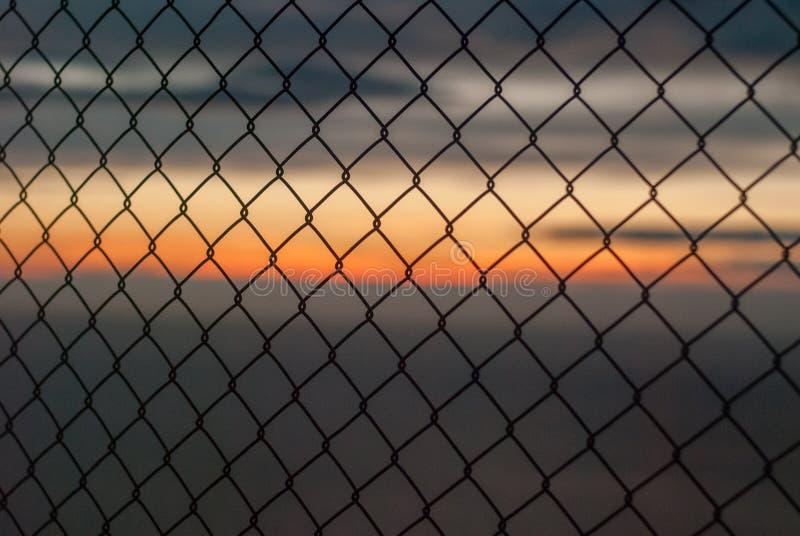Graue und orange Wolken bei Sonnenuntergang durch Metallgitter stockfotografie